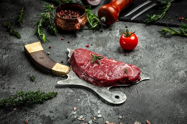 Raw beef rump steak served on old meat butcher on dark concrete background. top view.
