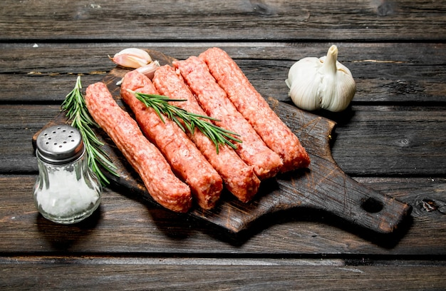 Raw beef sausages with spices and herbs. on a wooden.