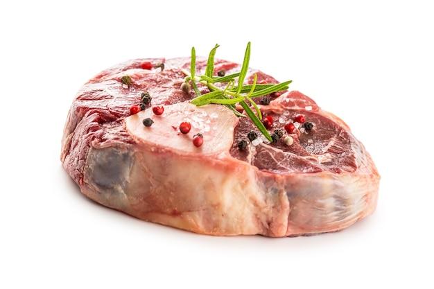 흰색 배경에 분리된 소금 후추와 로즈마리가 있는 생 쇠고기 정강이.