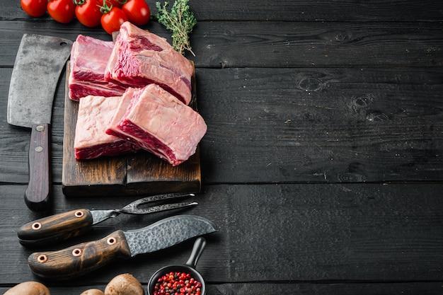텍스트 복사 공간 검은 나무 테이블 배경에 재료와 오래 된 정육점 칼, 원시 쇠고기 갈비 세트