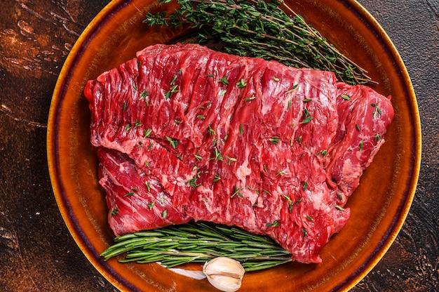 허브와 함께 소박한 접시에 원시 쇠고기 치마 고기 스테이크. 어두운 배경입니다. 평면도.