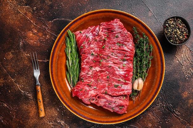 Стейк из сырой говяжьей юбки на деревенской тарелке с зеленью