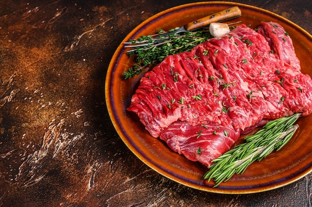 Raw beef skirt meat steak on a rustic plate with herbs