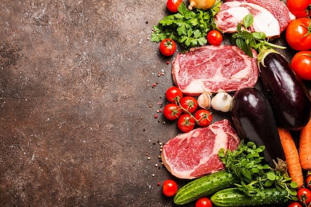 Сырая говядина ломтики мяса и овощей на темно-коричневом