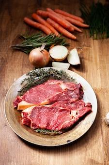 그릴 준비가 된 허브와 신선한 야채를 곁들인 생 쇠고기 스테이크. 비밀 재료. 천연 단백질.