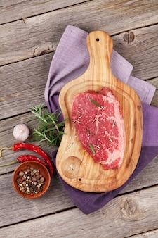 木製のテーブルに生のビーフステーキとスパイス。上面図