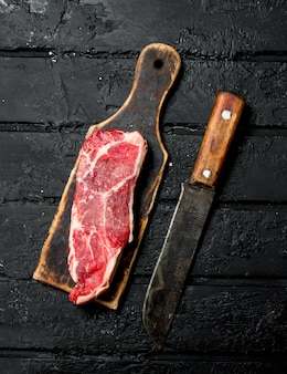 Raw beef steak on black wooden table.