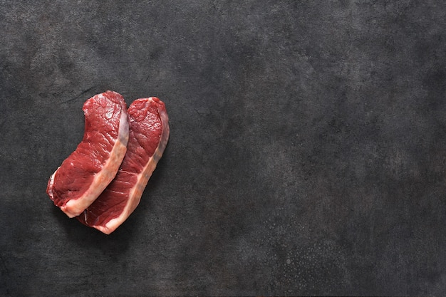 Сырой стейк из говядины на черном фоне бетона. вид сверху.