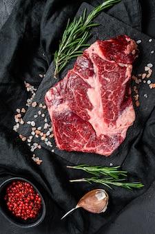 Сырой говяжий стейк на разделочную доску. органическое фермерское мясо. черный фон