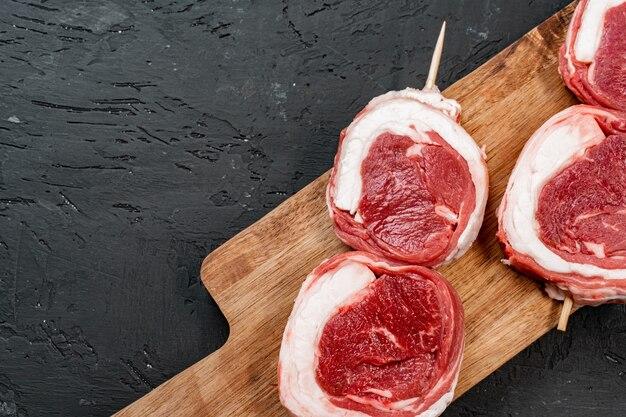 暗い木製のテーブルで生の牛肉ステーキ