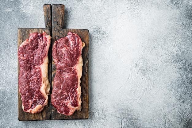 Сырой стейк из говядины, на сером фоне, плоский вид сверху с копией пространства для текста