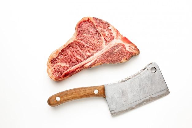 Сырой говяжий стейк на косточке с топором на белом фоне. вид сверху с копией пространства.