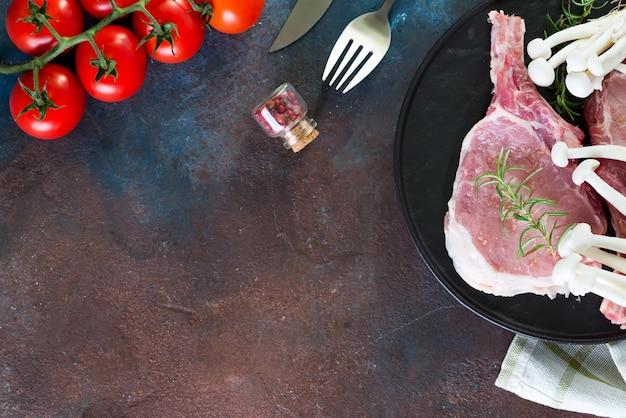 Сырой стейк из говядины на кости со свежими овощами на сковороде для гриля на бетонной поверхности