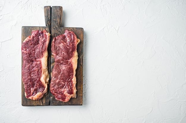 Сырой стейк из говядины на белом фоне, плоский вид сверху с копией пространства для текста