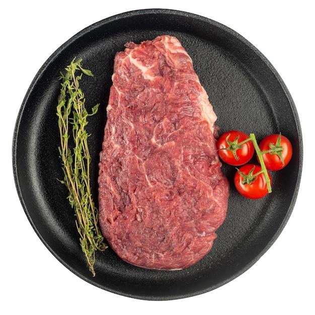 白い背景で隔離の鋳鉄鍋に新鮮な野菜、トマト、ハーブ、スパイスと生のビーフステーキ。上面図。
