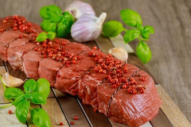 Сырой стейк из говядины с чесноком и базиликом на деревянной доске. красное мясо.
