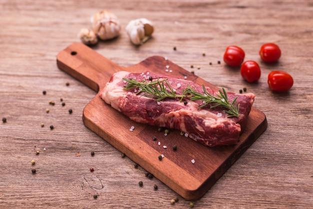 Сырой стейк из говядины с травами и специями на деревянных фоне