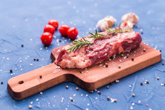 木製の背景にハーブとスパイスと生の牛肉ステーキ