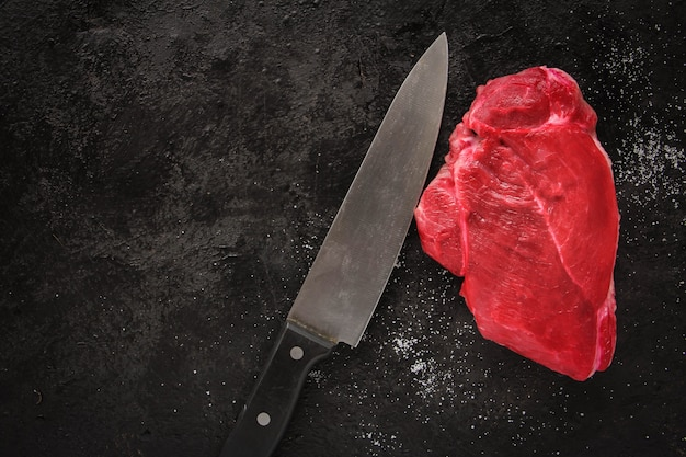 暗いスレート、石、またはコンクリートの背景にスパイスを添えた生のビーフステーキ。コピースペースのある上面図。