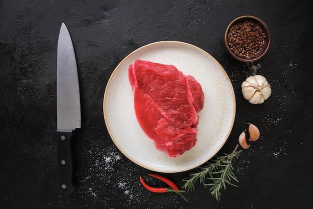 プレート、石、またはコンクリートの背景にスパイスを添えた生のビーフステーキ。コピースペースのある上面図。
