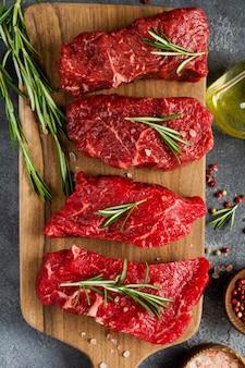 다크 슬레이트 또는 콘크리트 위에 향신료, 양파, 로즈마리를 곁들인 생 쇠고기 스테이크.