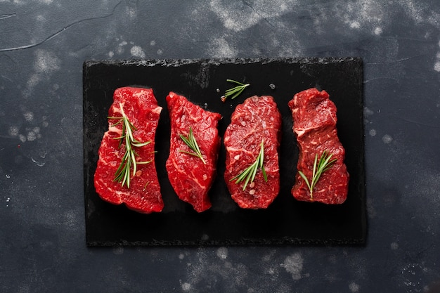 Raw beef steak with spices, onions and rosemary on dark slate or concrete wall. top view
