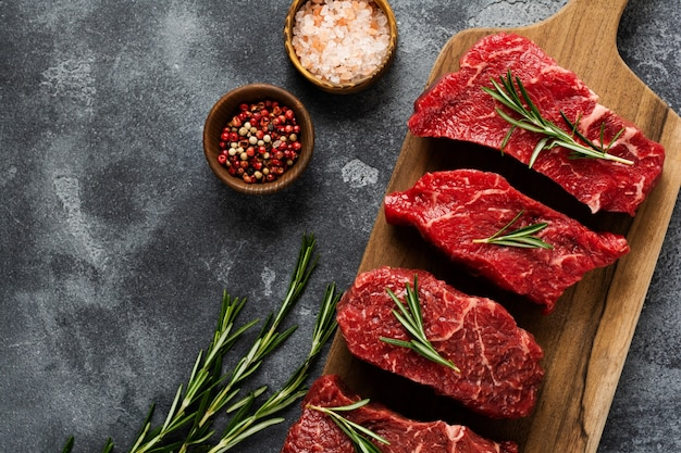 Raw beef steak with spices, onions and rosemary on dark slate or concrete.