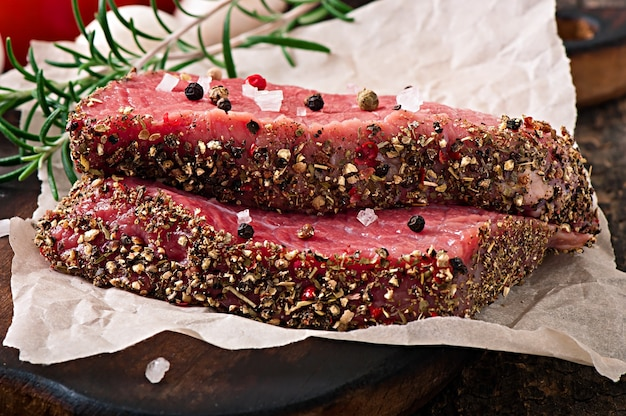 Raw beef steak with spices and a sprig of rosemary