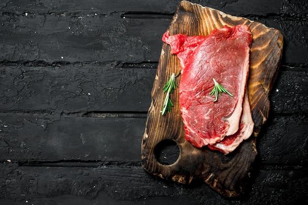 Raw beef steaks on dark rustic table.