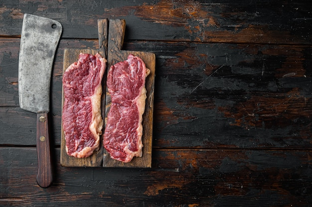 Raw beef steaks, on old dark  wooden table background, top view flat lay  with copy space for text
