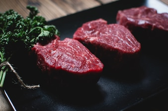 Raw beef steaks on a black plate