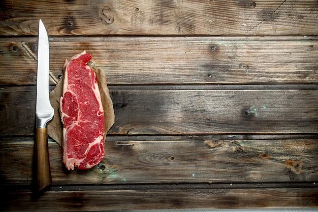 Raw beef steaks on rustic table.