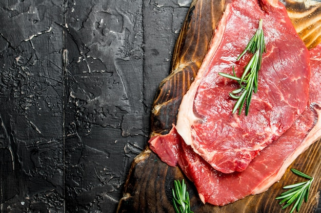 Raw beef steaks with fragrant rosemary. on a black rustic background.