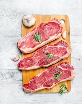 향신료와 허브와 함께 원시 쇠고기 스테이크. 소박한 테이블에.