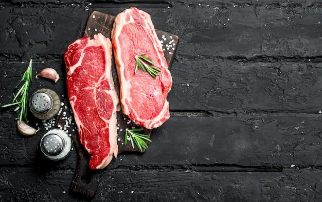 향신료와 소금을 곁들인 생 쇠고기 스테이크. 검은 소박한 배경.