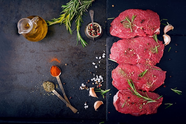 Raw beef steaks with spices and rosemary. flat lay.top view