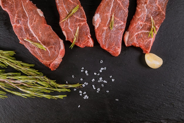 Raw beef steaks with spices and rosemary. flat lay.