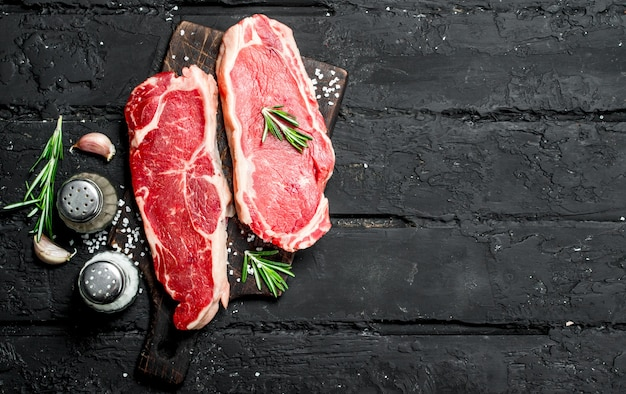 Raw beef steaks with spices and salt. on a black rustic background.