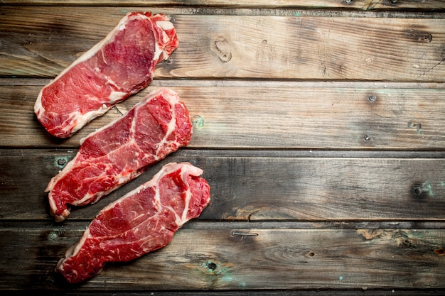 Raw beef steaks . on a wooden background.