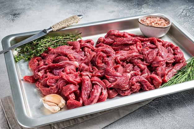 원시 쇠고기는 로즈마리와 백리향이 든 주방 쟁반에 조각을 냅니다. 흰 바탕. 평면도.