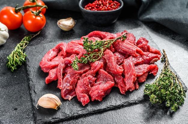 Сырое мясо бефстроганов на черном столе.