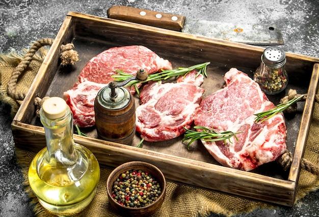 ハーブとスパイスを添えた生の牛肉。素朴な背景に。