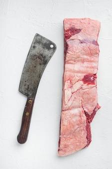원시 블랙 앵거스 차돌박이 쇠고기 갈비 세트, 흰색 돌 배경에 오래 된 정육점 칼 칼, 평면도 평면 누워