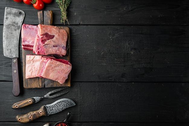 원시 블랙 앵거스 차돌박이 쇠고기 갈비 세트, 재료 및 오래된 정육점 칼, 검은 나무 테이블 배경, 평면도 평면 누워, 텍스트 복사 공간