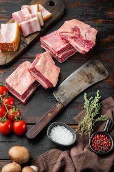 원시 블랙 앵거스 차돌박이 쇠고기 갈비 세트, 재료, 오래 된 어두운 나무 테이블 배경에 오래 된 정육점 칼 칼