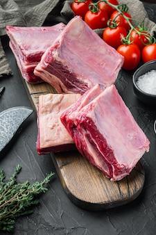 검은 돌 배경에 재료와 함께 원시 블랙 앵거스 차돌박이 쇠고기 갈비 세트