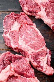Сырые мясные стейки блэк ангус прайм, набор, вырез рибай, на фоне старого темного деревянного стола