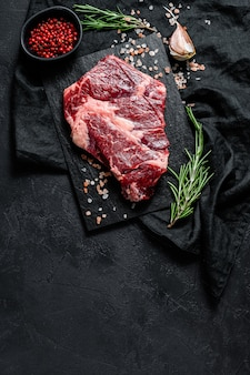 생 블랙 앵거스 스테이크. 유기농 농장 쇠고기 블랙 앵거스. 검은 벽. 텍스트를위한 공간