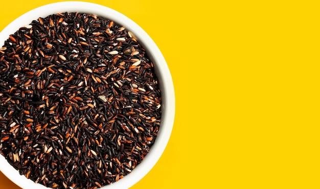Raw black sicky rice on yellow background