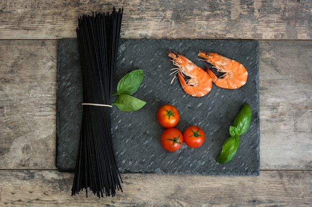 Raw black spaghetti with prawns, tomatoes and basil on wooden